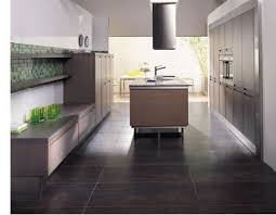 A very modern kitchen with large square slate tile flooring, sleek European  wood cabinets and