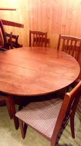 wooden table that is round when two leaves are out and four material base chairs