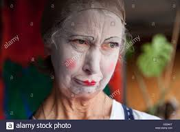 elderly woman in whiteface clown makeup pulls series of funny faces picture 7 of 8