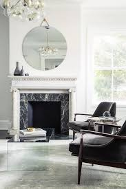 pair of black velvet accent chairs facing a lucite waterfall coffee table atop a gray rug placed in front of an original white marble fireplace accented