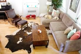 brown and whit large cowhide rug living room decoration brown rustic antique table with wheels light brown maple wood flooring l shaped beige fabric cushion