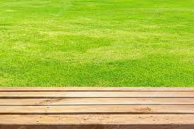 empty wooden deck table on green grass background stock photo