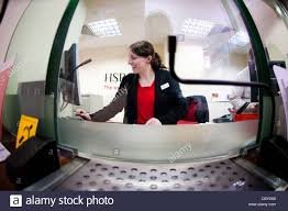 A Woman Bank Teller Working Behind The Counter At A Branch Of Hsbc