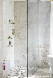 fantastic bathroom features corner seamless glass shower clad in light gray stone fitted with a small shower bench atop a mosaic shower floor