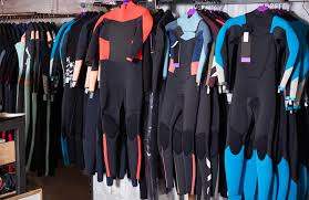 colorful wetsuits in displa in a