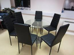 circular glass dining table with chrome base together with 6 chairs in black leather effect