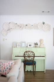 white flower wall decor hanging on a living room wall above a mint piano