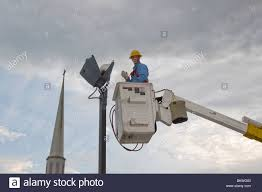 How To Change A Parking Lot Light Bulb Man Replacing Parking Lot Light Bulb From Bucket Truck Stock