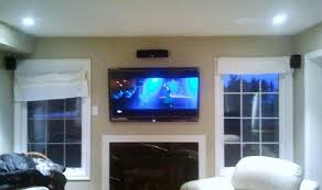 flat screen tv on wall with surround sound. all wires concealed behind the over fireplace flat screen tv and surround sound installation. tv on wall with r