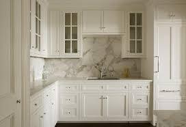 white shaker cabinets with gray and white marble slab backsplash