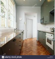 modern white and gray kitchen. Parquet Flooring In Modern White Galley Kitchen With Gray Fitted Units And Granite Worktops