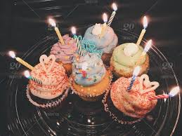 Six Different Gourmet Cupcakes With Lit Birthday Candles Sit On A
