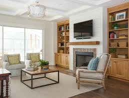 troy lighting sausalito pendant accents a coffered ceiling illuminating a white shiplap fireplace wall lined with a flat panel television and speaker