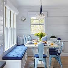 metal chairs with cushions. bungalow dining space with white trestle table and blue metal chairs cushions a