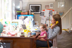 running home office. Mother With Daughter Running Small Business From Home Office Stock Images