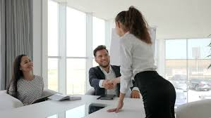 spacious insurance office design. girl shake hands on interview in modern office female candidate during job into large spacious insurance design