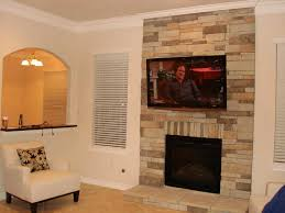 tv mounting over fireplace with stone wall