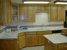 light wood kitchen with white countertops and glass cabinets