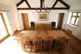 the 2 4 2 9m tallinn erfly extending european oak table shown with 10 stunning winchester leather chairs with dark brown pads d at 1629