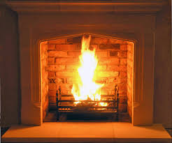 hand carved limestone mantel with reclaimed brick slip chamber installed by scarlett design a fireplace