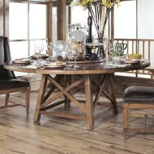 a large trestle table with x motif base pairs with upholstered back chairs with nail head trim in the dining room an industrial metal base supports a 60