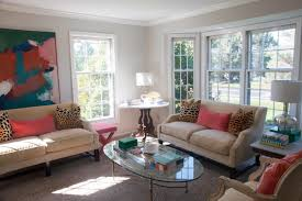 two sofas with large abstract painting and glass coffee table in small living room showing furniture