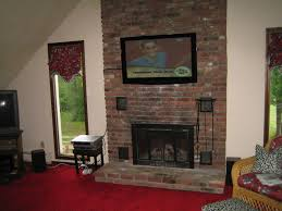 brown and cream living room decor ideas black fireplace on the brown brick wall completed with large tv above on the middle of glass windows