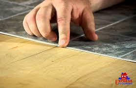 carefully install vinyl tiles over wood floors