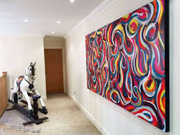 large painting hanging by a rocking horse