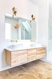 floating unfinished wood credenza and cabinets underneath double basin sinks with wall mounted brass sink bathroom vanity barnwood mirror oyster pendant lights