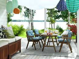 wooden table and chairs with blue and white seat cushions on a colourful outdoor terrace overlooking