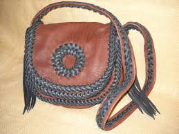 this handmade custom leather purse was made with mahogany pieces braided together with dark brown laces