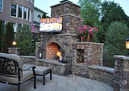 outdoor kitchen with custom fireplace and big screen tv