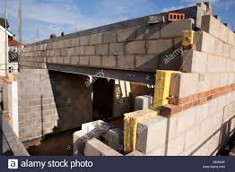 self building house, constructing upper floor, with traditional concrete  block construction above steel lintel