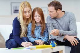 Single parent helping young daughter with her homework in the kitchen     Stock Image