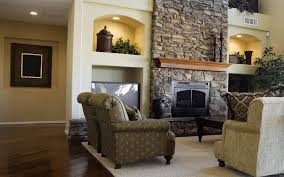 ordinary fireplace on stone wall with patterned armchair on cream carpet plus green plants on the