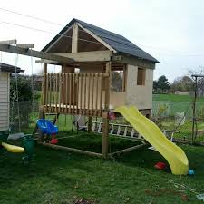 a playhouse with an attached swing set