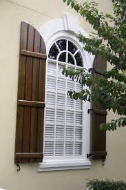 Board and Batten Exterior Shutters stained wood with bright white window.