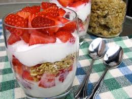 strawberry yogurt and granola parfaits in a tall gl with spoons