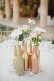 save up various bottles and bedazzle them with metallic paints and glitter to make a myriad of vases that will add a modern funky look to your reception