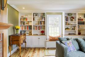 built in window seat and storage with flanking custom bookcases and pine floors in this groton