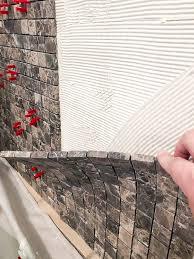 applying mosaic tile to front of bathtub surround