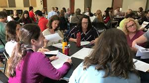 image of employees having discussions while seated at round tables at a ttc project fundamentals training