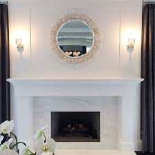 stunning living room fireplace boasts a white marble surround and a contrasting gray herringbone firebox under a white mirror illuminated by nickel and