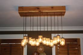 mason jar lighting fixtures and chandeliers with cedar bases and wooden panel on the ceiling for