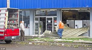 technicians from twin city glass inspect wind damage at the entrance of the manchester brothers
