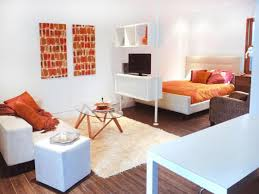 fabulous bedroom and living room iin the one space with orange bedding plus  elips glass table on ...