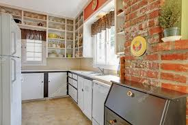 old simple white kitchen with brick wall stock photo