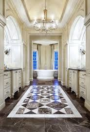 mediterranean master bathroom with tray ceiling chandelier freestanding tub and tile flooring