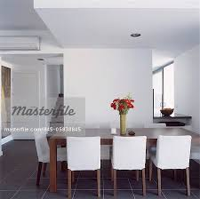 white upholstered chair around wooden table in contemporary white dining room stock photo